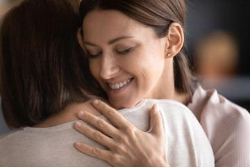 Smiling adult grown up daughter with closed eyes hugging mature mother close up, family enjoying tender moment together, two generations bonding, trusted good relations, support and care