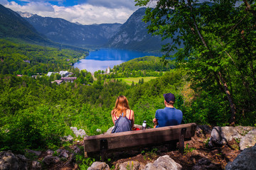 Wall Mural - Tourist couple enjoying the view from the bench, lake Bohinj