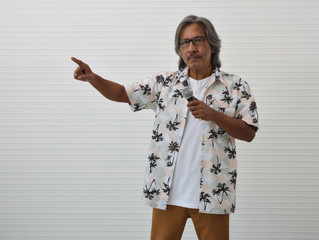 Senior traveler asian man wearing glasses, summer shirt and brown shorts speaking with microphone and pointing finger up standing over white wall background, Business summer holiday concept