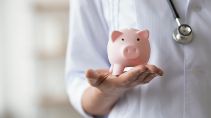 Woman doctor wearing white coat and stethoscope holding piggy bank box in hands. Healthcare...