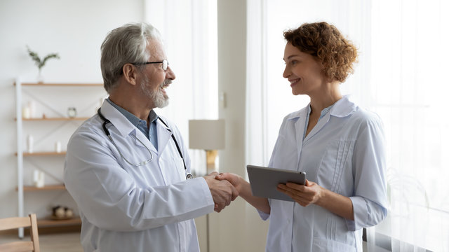 Happy senior old male physician handshaking young female nurse thanking for help in professional teamwork. Two doctors team shake hands expressing gratitude, trust in medical collaboration concept.