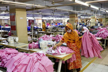 A woman works in a garment factory, as factories reopened after the government has eased the restrictions amid concerns over coronavirus disease (COVID-19) outbreak in Dhaka