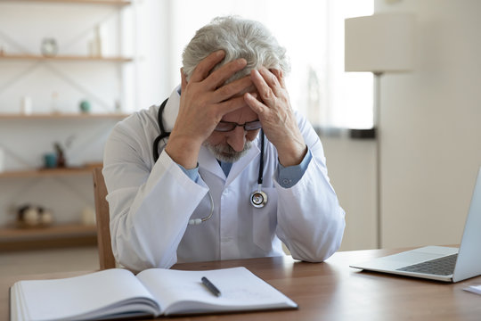 Tired depressed old male doctor feels desperate thinking of medical problem feels burnout at work. Worried upset senior physician regrets medical malpractice suffers from guilt sits alone in office.