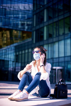 Full length shot of careworn businesswoman wearing face mask for prevention while talking with somebody on her mobile phone on the street.