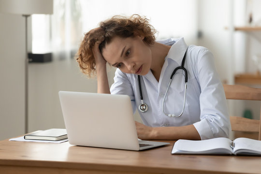 Stressed young female doctor looking at laptop reading bad news online worried of mistake at workplace. Unhappy professional physician in tension feeling tired solving computer problem at work.