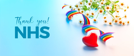 """Red heart and curled rainbow ribbon. Rainbow text """"Thank you NHS"""" on lightbox. Public support of NHS doctors and nurses, medical personnel teams fighting coronavirus pandemics Covid-19."""