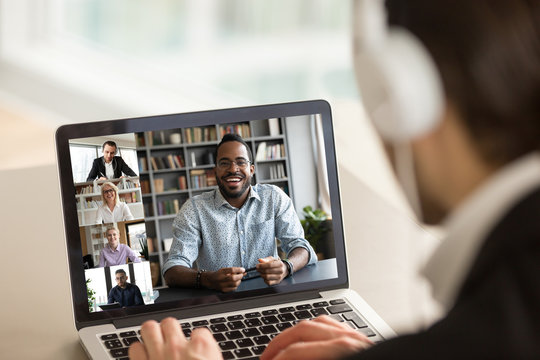 Back view of male employee in headphones have online webcam conference on computer with diverse colleagues, businessman talk speak on video call on laptop from home with multiracial coworkers