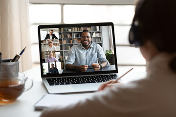 Back view of female employee have webcam conference on computer with multiracial colleagues, woman...