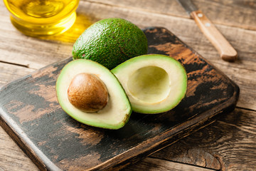Fresh green avocado and oil on wooden table