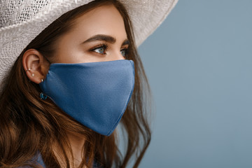 Woman wearing stylish protective face mask, posing on blue background. Trendy Fashion accessory during quarantine of coronavirus pandemic. Close up studio portrait. Copy, empty space for text Fotomurales