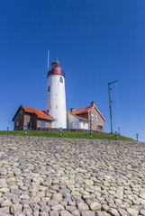 Fotomurales - White lighthouse and houses on the top of the dike in Urk, Netherlands