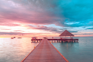 Wall Mural - Amazing sunset landscape. Picturesque summer sunset in Maldives. Luxury resort villas seascape with soft led lights under colorful sky. Dream sunset over tropical sea, fantastic nature scenery