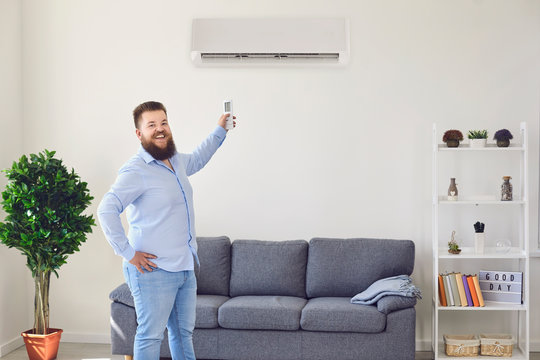 Fat funny man holding an air conditioning control panel at home. Air conditioner.