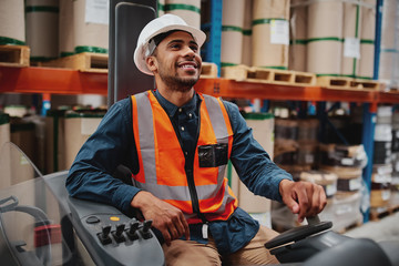 Happy forklift driver focused on carefully transporting stock from shelves around the floor of a large warehouse wearing a white helmet and vest Fotobehang