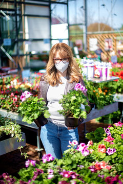 Mature woman buying plants while wearing face mask in the garden store