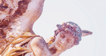 Fototapete - Fragment of ancient stone statue of beautiful angel flies in the sky