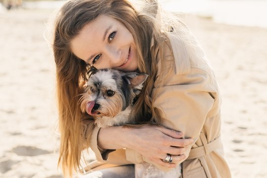 Caring for animals. A beautiful girl hugs a cute dog. Walking with the dog. Friendship with a dog