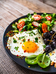 Continental breakfast - sunny side up egg, blue cheese, grapes and vegetable salad