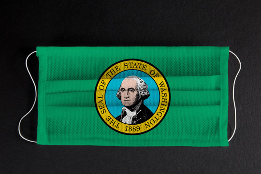 Coronavirus Covid-19 in the State of Washington. Flag of the State of Washington printed on medical mask on black background. Coronavirus update in Seattle. State healthcare concept.