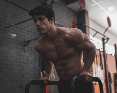 Young, shirtless, muscular athlete doing some dips in parallel bars in the gym. Professional calisthenics athlete working out