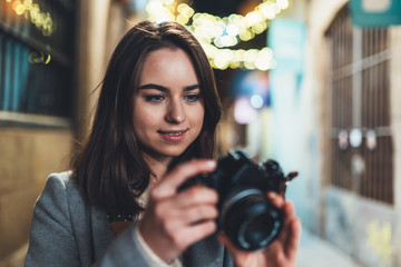 Fotomurales - Photographer girl with retro camera take photo on background bokeh light in night city, Blogger photoshoot concept, photo hobby. Outdoor portrait of young smile woman with video technology.