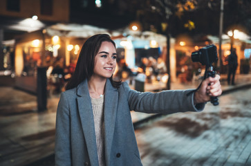 Fotomurales - Girl vlogger recording with digital camera. Smiling woman taking selfie video on light night city. Traveler making video for her blog. Vlogger uses photo camera for shoot social media