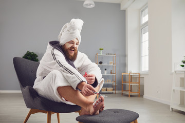 Fotorolgordijn Pedicure Funny pedicure concept. Funny fat man in a bathrobe and a towel paints his nails