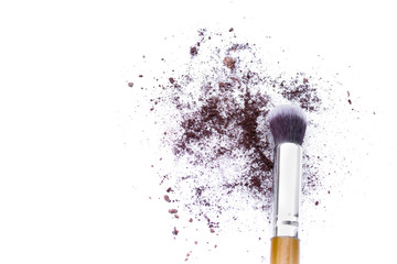 Make up brushes and brown eye shadows on black background.
