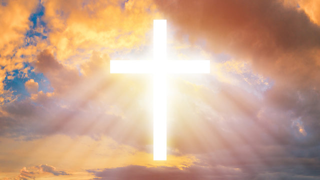 The Christian cross among the clouds. Religion. Support of the faithful. Religious signs and symbols. Light pours from the cross in the sky.
