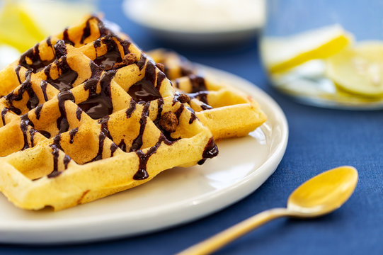 Close-up belgian waffles topped with chocolate sauce in a plate aside a golden spoon and golden tongs on a blue cloth background.