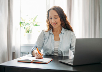 Adult smiling brunette woman doing notes in daily book with opened laptop. She study something with online course at the home