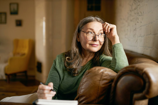 Stylish inspired middle aged woman writer wearing glasses sitting in leather couch with pen making notes. Attractive mature female artist sketching or teacher preparing tasks for online lessons
