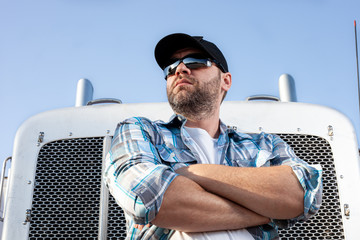Confident semi truck driver wearing plaid shirt and black baseball cap  stands with arms crossed in front of big rig. Portrait of professional looking trucker. Blue collar jobs in transportation.