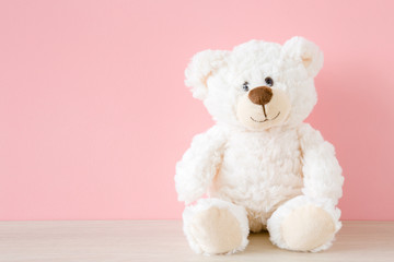Smiling white teddy bear sitting on table at pastel pink wall background. Kids best friend. Front view. Close up. Fotomurales