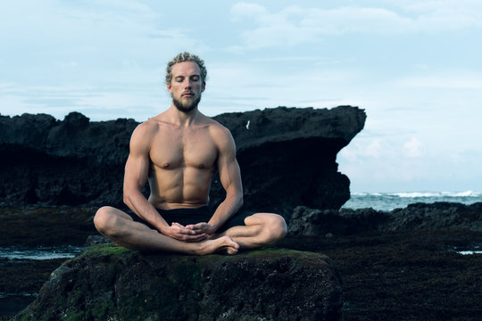 Athlete man practicing yoga outdoors photograph