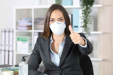 Executive wearing mask with thumbs up looking camera
