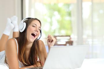 Girl with headphones singing listening music on laptop