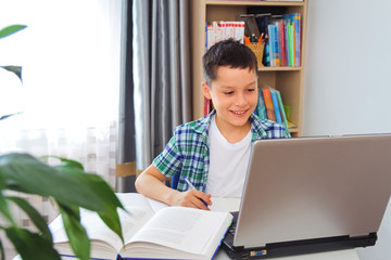 Distance learning online education. Schoolboy boy studies at home with laptop and does school homework. Training books and notebooks on table