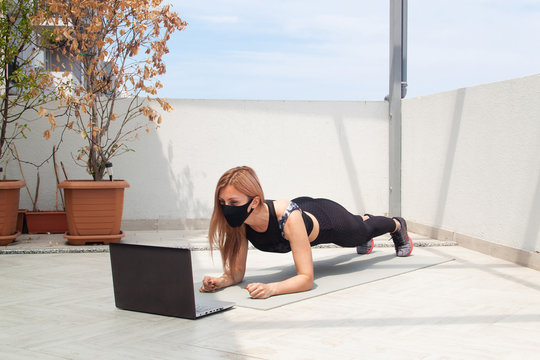 Woman in mask and with laptop  on the mat on the balcony doing plank and exercises. Online tranning in quarantine.