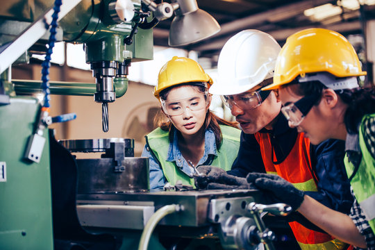 Asian male technician manager showing case study of factory machine to two engineer trainee young woman in protective uniform. teamwork people training and working in industrial manufacturing business