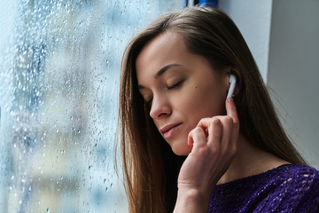 Young woman music lover with closed eyes in wireless earbuds enjoys and listens to soothing calming relaxing music during standing by the window with raindrops in rainy fall weather Fotobehang