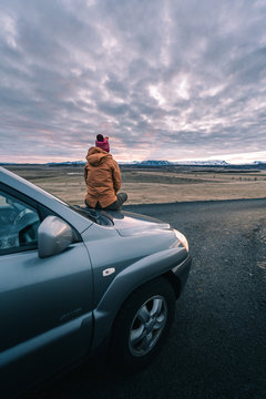 Road trip is calling. Time for the road adventure begins. A young solo female adventure traveler in a nature with beautiful sunset sky. Iceland travel