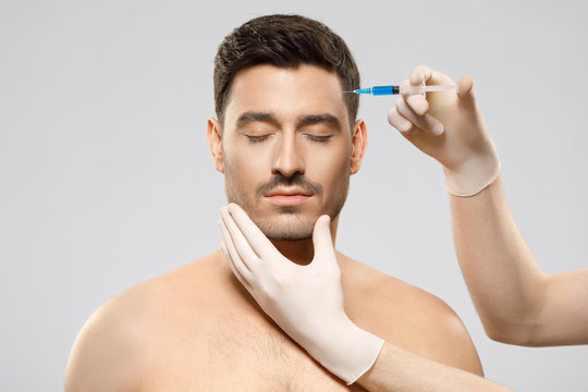 Young shirtless man receiving beauty injection in forehead to remove wrinkles, face held by hands of cosmetologist, isolated on gray background. Plastic surgery concept