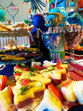 """Festive children""""s table with transparent glasses sandwiches caces and sweets."""