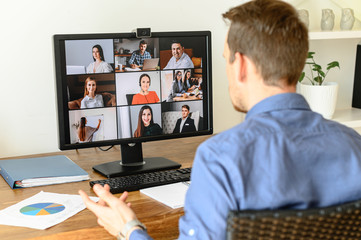 Virtual conference with employees. A young man in formal shirt using pc for video call, he has video meeting with several people together. Remote work concept