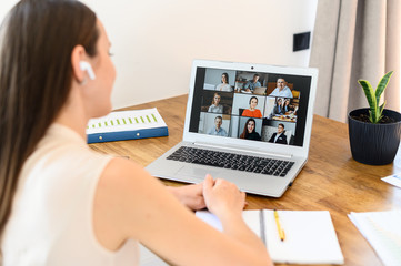 Virtual video conference, online meeting with a many employees together. A young woman is communicating via video call with coworkers, a several webcam shot of people on the laptop screen