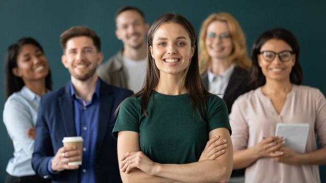 Close up headshot portrait of happy businesswoman hands crossed posture. Different age and ethnicity businesspeople standing behind of female company chief business. Leader of multi-ethnic team