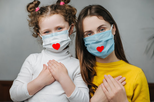 Mothers and daughter holding hands on breast sit on bed, wear face mask with heart on it as a way to show thank gratitude to doctors and nurses for help in the fight against the disease. Covid-19