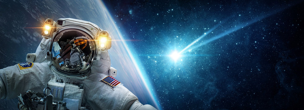 Astronaut in orbit of planet Earth against the background of a falling meteorite, asteroid, comet. The concept on the theme apocalypse, armageddon, doomsday,. Elements of this image furnished by NASA.