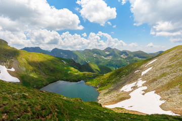 beautiful nature of romania mountains. lake capra in the valley. hills covered in grass, rocks and snow. wonderful summer sunny day with gorgeous cloudscape